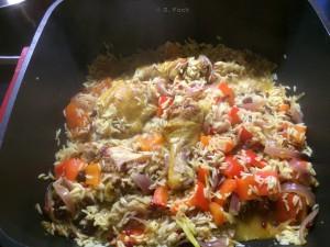 Hähnchen, Paprika und Reis schmurgeln vor sich hin.
